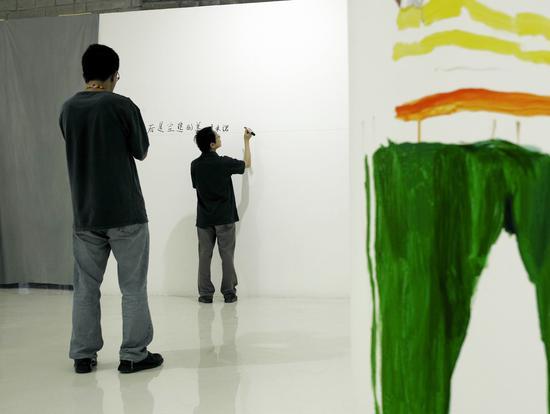 2006年9月为《多米诺》展览在墙上写前言,刘小东为尹吉男画速写。